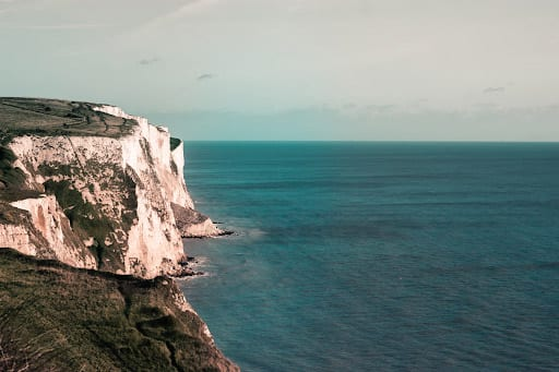 photo of white cliffs overlooking a blue green sea
